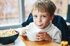 Trinkmilch des kaukasischen Kinderkinderjungen von der weißen Schale, die das Frühstücksmittagessen isst Lizenzfreie Stockfotos
