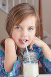 Trinkmilch des kleinen Mädchens Lizenzfreie Stockfotos