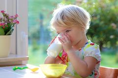 Trinkmilch des Kleinkindmädchens vom Glas Stockbilder