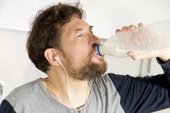 Trinkmilch des Mannes morgens in der Küche von der Flaschennahaufnahme stockfotografie