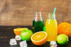 Trinkt Orangensaft auf Estragon in den Flaschen mit frischer Frucht lizenzfreies stockbild