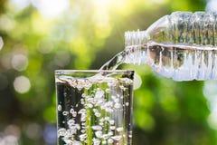 Trinkwasser, das aus Flasche in Glas auf unscharfem neuem grünem Natur bokeh Hintergrund gießt stockfoto