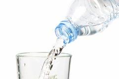 Trinkwasser, das in die Flasche fließt. Lizenzfreie Stockfotografie