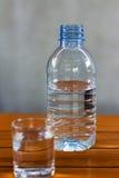 Trinkwasser in den Glas- und Plastikflaschen auf einem Holztisch Stockfotografie
