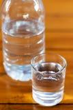Trinkwasser in den Glas- und Plastikflaschen auf einem Holztisch Stockbild