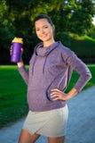 Trinkwasser der Eignungsfrau nachdem dem Laufen in Park Lizenzfreie Stockfotografie