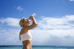 Trinkwasser der Frau auf Strand. Lizenzfreies Stockfoto