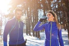 Trinkwasser der Frau im Holz auf Training lizenzfreies stockbild