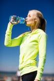 Trinkwasser der Frau, nach dem Handeln, trägt draußen zur Schau Stockfotografie
