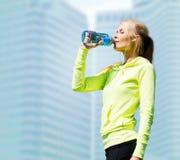 Trinkwasser der Frau, nach dem Handeln, trägt draußen zur Schau Lizenzfreies Stockbild