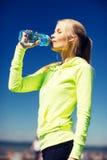 Trinkwasser der Frau, nach dem Handeln, trägt draußen zur Schau Stockbild