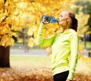 Trinkwasser der Frau, nach dem Handeln, trägt draußen zur Schau Lizenzfreies Stockfoto