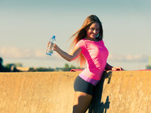 Trinkwasser der Frau nach der Sportturnhalle im Freien lizenzfreie stockbilder