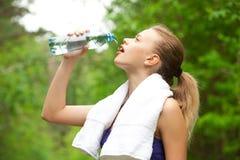 Trinkwasser der Frau nach Eignung stockfotos