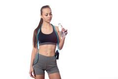 Trinkwasser der Frau und halten Springseil auf weißem Hintergrund Lizenzfreie Stockbilder