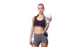 Trinkwasser der Frau und halten Springseil auf weißem Hintergrund Stockbild