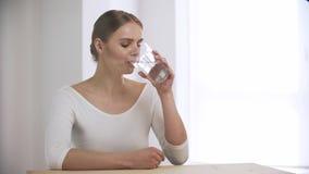Trinkwasser der Frau vom Glas und Betrachten der Kamera stock video footage
