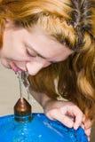 Trinkwasser der Frau von einem Straßenhahn lizenzfreie stockfotografie