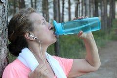 Trinkwasser der gesunden reifen Frau mit laufendem Trainingsnazug und Tuch Lizenzfreies Stockbild