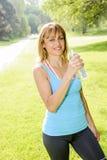 Trinkwasser der glücklichen Frau beim Ausarbeiten Stockfotografie