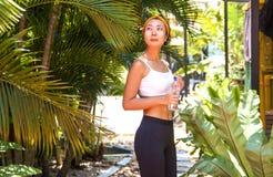 Trinkwasser der jungen Frau des Sports asiatischen nach dem Handeln ihrer Morgenübungen und -betriebs in einem Park nahe der Palm stockfotos