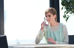 Trinkwasser der jungen Frau an einem Freien restaura Lizenzfreie Stockbilder