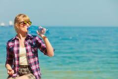 Trinkwasser der jungen Frau im Freien Stockbilder