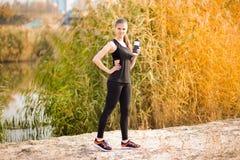 Trinkwasser der schönen Eignungsathletenfrau nach arbeiten das Trainieren auf Herbstpark aus lizenzfreies stockbild