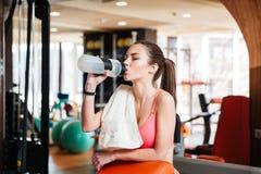 Trinkwasser der Sportlerin auf Training in der Turnhalle stockbilder
