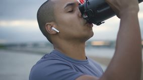 Trinkwasser des Afroamerikanerathleten von der Flasche stock footage