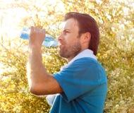 Trinkwasser des aktiven Mannes nach Training im Freien Stockbild