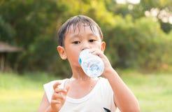Trinkwasser des asiatischen Jungen von der Plastikflasche nach einer Übung Lizenzfreies Stockfoto