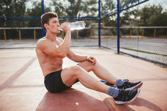 Trinkwasser des Athleten nach einem Training Lizenzfreie Stockfotografie