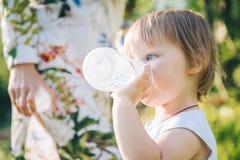 Trinkwasser des Babys von der Babyflasche Lizenzfreies Stockfoto