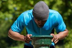 Trinkwasser des durstigen Afroamerikanermannes Stockfotografie