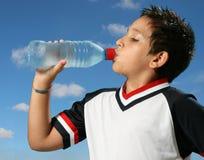 Trinkwasser des durstigen Jungen heraus lizenzfreies stockfoto