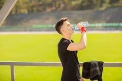 Trinkwasser des Eignungsmannes von der Flasche Durstiger Athlet, der kaltes Erfrischungsgetr?nk nach intensiver ?bung hat lizenzfreie stockfotos