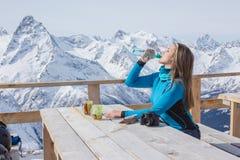 Trinkwasser des Frauensnowboarders draußen gegen einen Hintergrund O Stockbilder