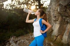Trinkwasser des hübschen Wanderermädchens Formschöner Frauentourist mit Trinkwasser des Rucksacks in der Natur Kaukasische Frauge Stockbild
