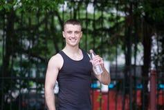 Trinkwasser des hübschen Athletenmannes Lizenzfreie Stockfotos