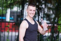 Trinkwasser des hübschen Athletenmannes Stockfotos