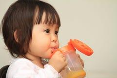 Trinkwasser des japanischen Babys Stockfotos