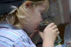 Trinkwasser des Jungen stockfotografie
