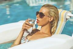 Trinkwasser des jungen Mädchens in einem Pool Lizenzfreies Stockfoto