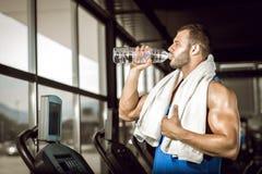 Trinkwasser des jungen Mannes in der Turnhalle Stockbilder
