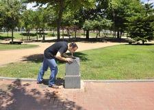 Trinkwasser des jungen Mannes in einem Brunnen Lizenzfreie Stockfotos