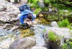 Trinkwasser des jungen Mannes von einem Frühling Stockbild