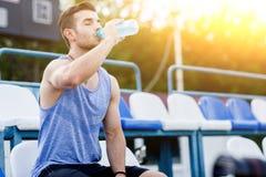 Trinkwasser des kaukasischen Mannes mit seinem mustert geschlossenes nach Übungen Stockfoto
