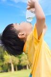 Trinkwasser des kleinen asiatischen Jungen von der Plastikflasche Stockfotografie