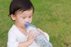 Trinkwasser des kleinen asiatischen Mädchens von der Plastikflasche Stockfotografie